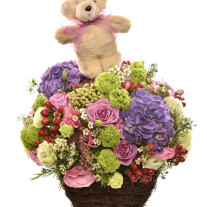Arrangement of cut flowers with Teddy Bear